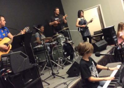 Mel Booker Music Students and Instructors performing at a Rock Shop